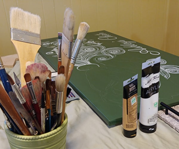 dining room table with art supplies and canvas