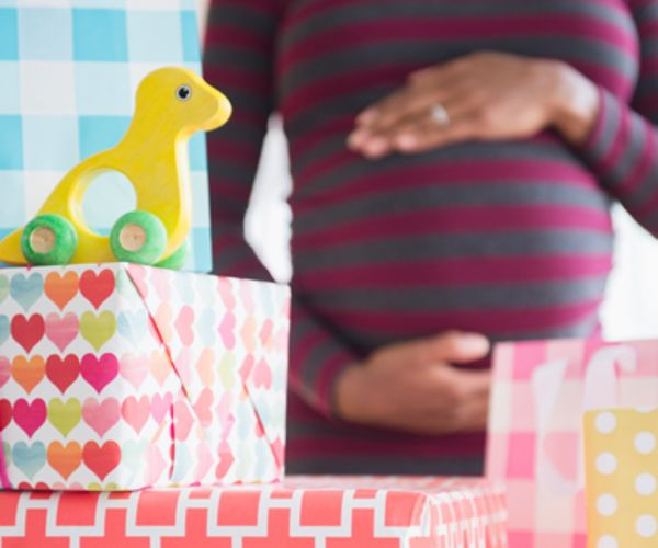 Woman holds baby bump, stack of gifts in foreground.