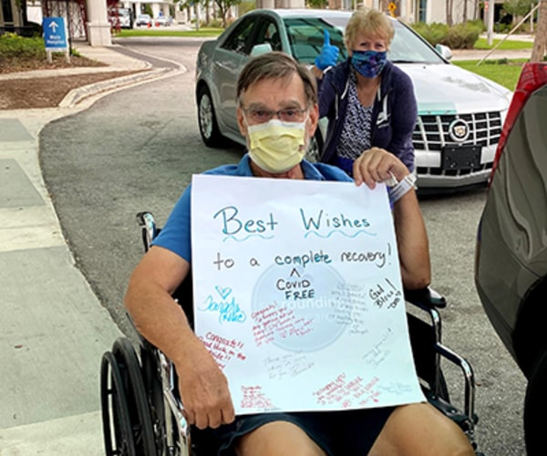 Man in wheelchair holding best wishes sign