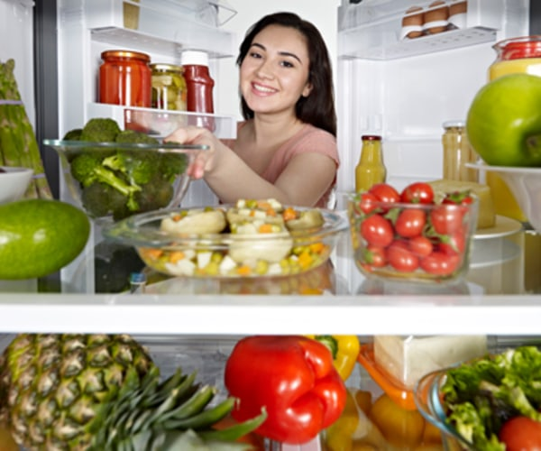 woman looking at healthy foods in her refrigerator