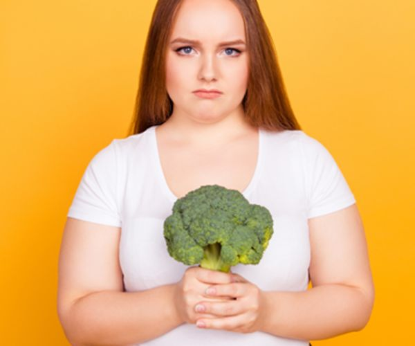 Girl looking sad holding a stalk of broccoli