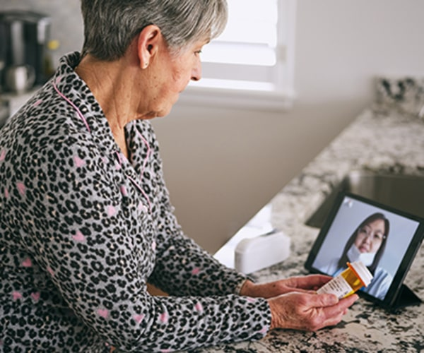 Older woman using Ipad to talk to her doctor online