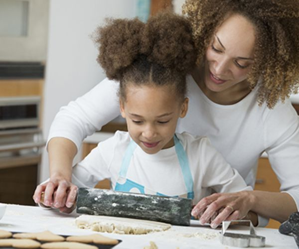 A mother and daughter roll out cookie dough together while baking.