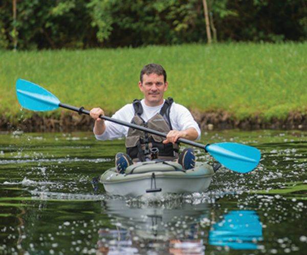James enjoying kayaking in a lake.