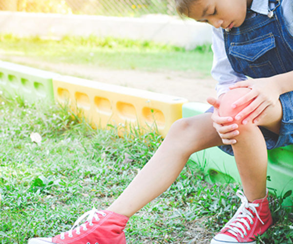 child holding knee in pain