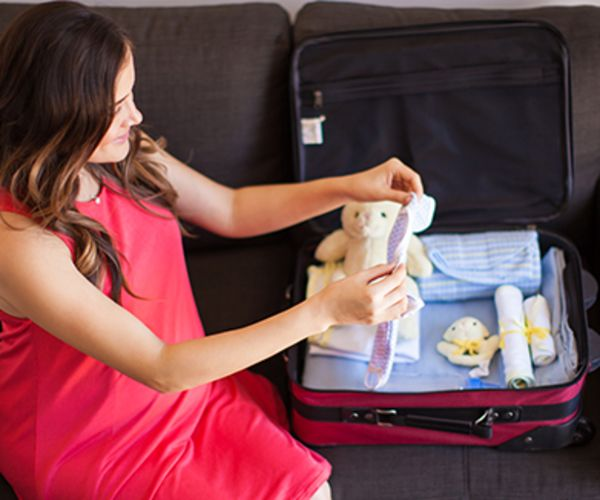 Pregnant woman packing suitcase for hospital.