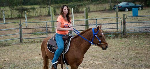 Woman riding a horse at a ranch