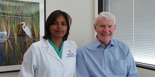 Doctor standing with patient for photo