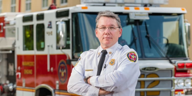 police chief and stroke survivor poses in front of fire truck
