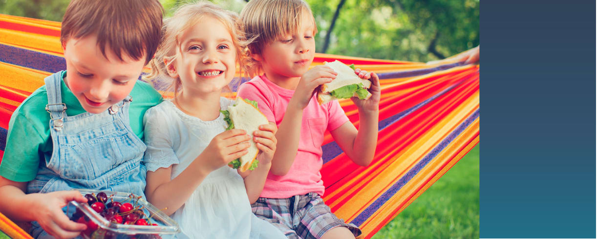 Three school-age children sitting on a striped hammock outside eating sandwiches with smiles on their faces