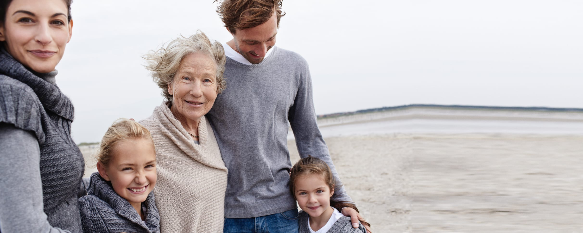 A grandmother at the beach with her children and grandchildren, all smiling at the camera.