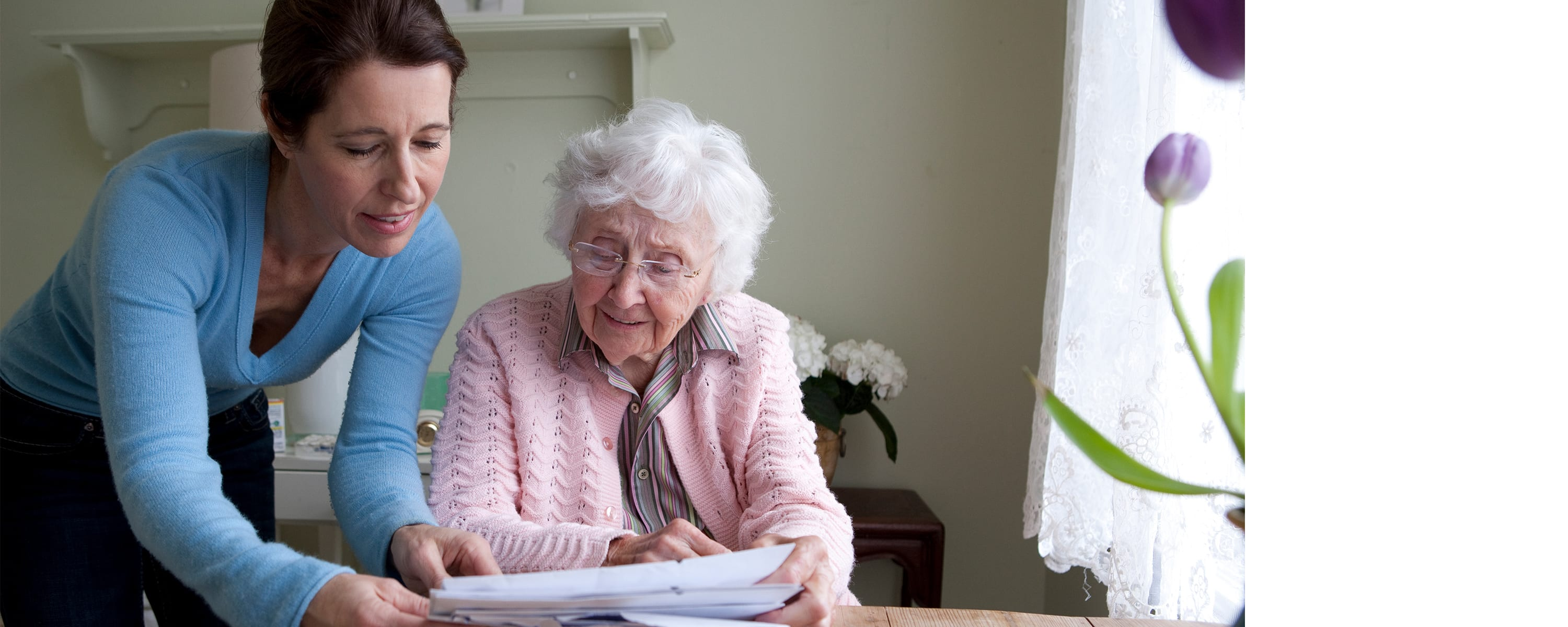 woman looking over paperwork with an elderly woman