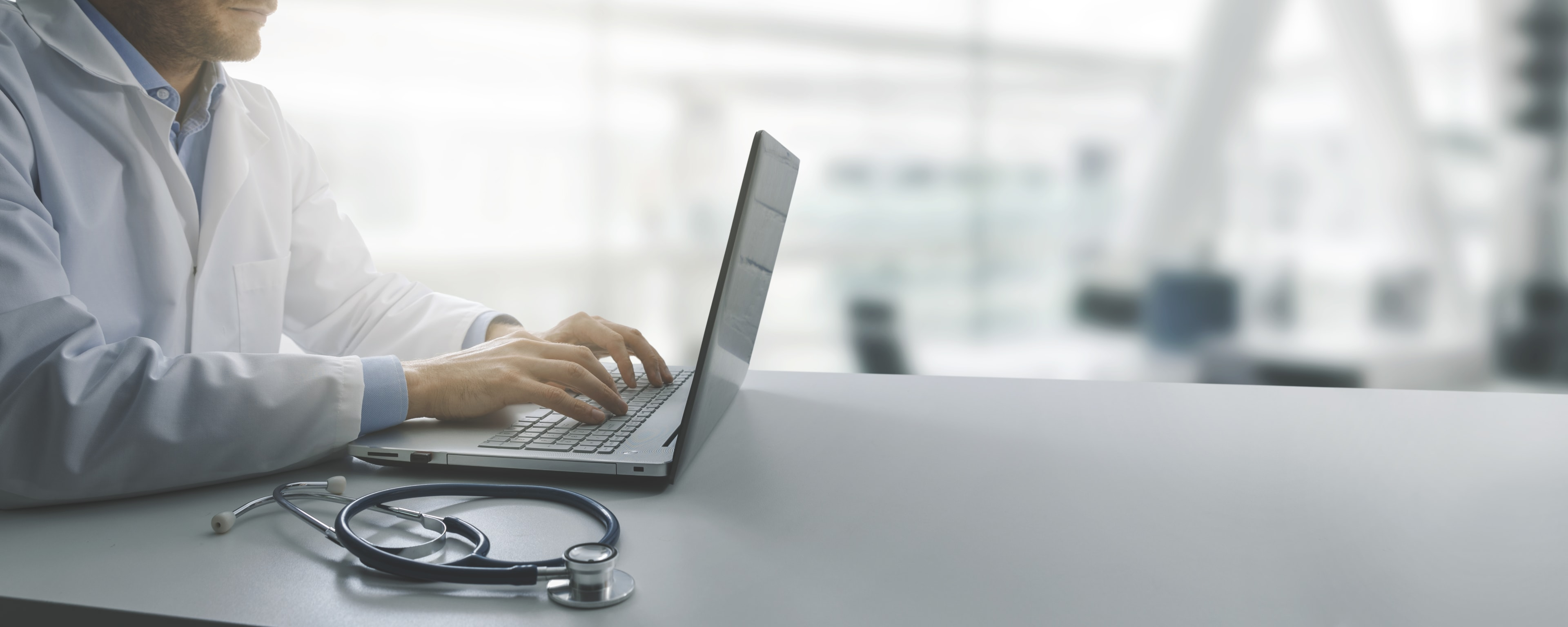 a healthcare provider typing on a laptop computer with a stethoscope placed on the table next to the laptop.