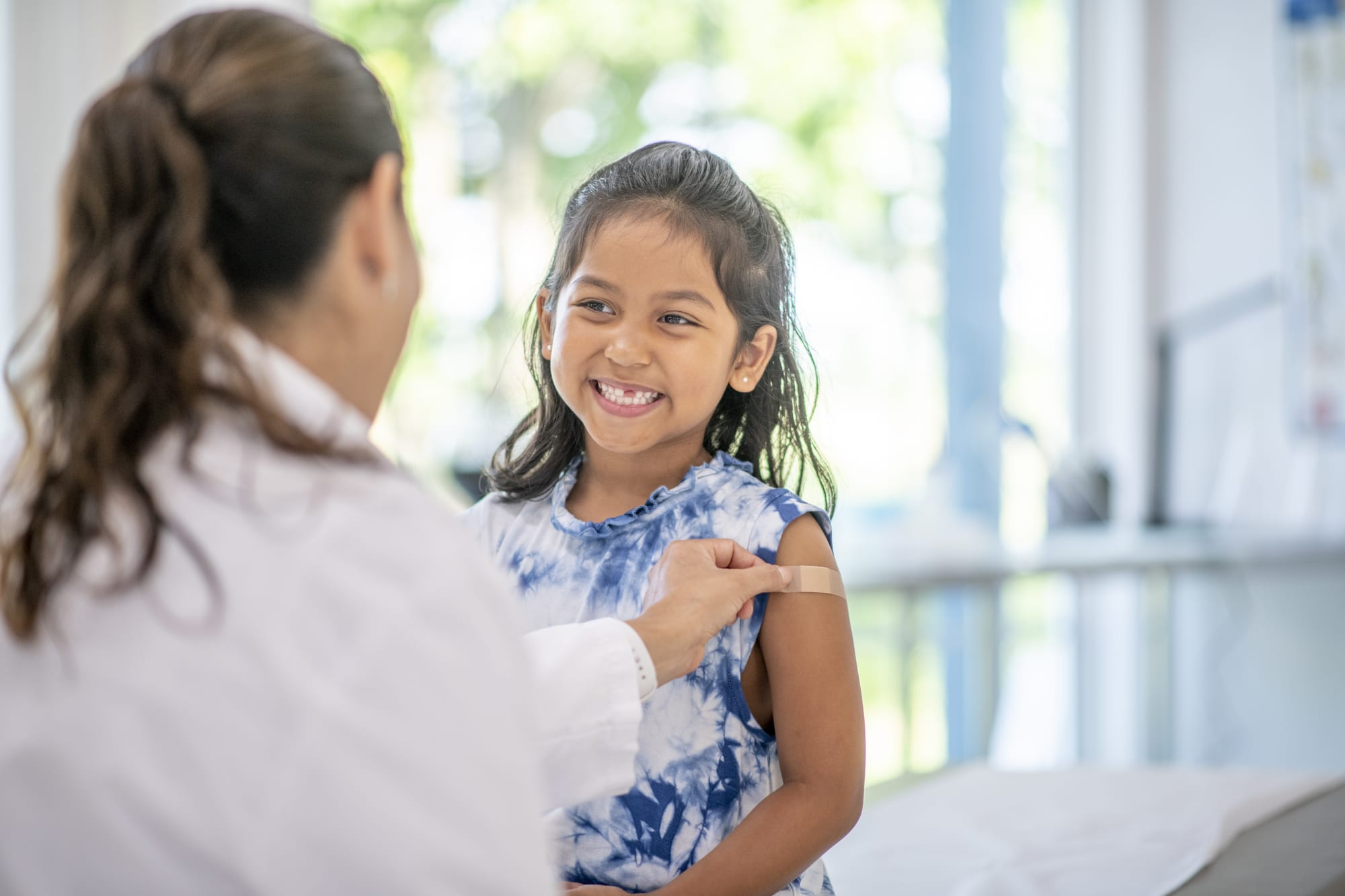 child interacts with the female Hispanic doctor at a medical appointment.