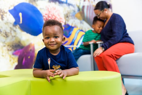Little boy smilign while leaning on ottoman in ER lobby