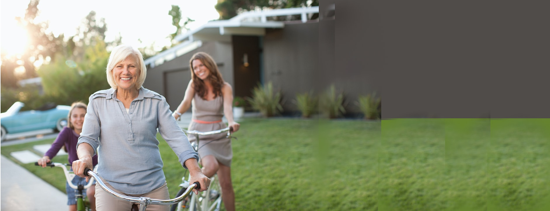 woman in her front yard on a bike with her daughter and grandchild