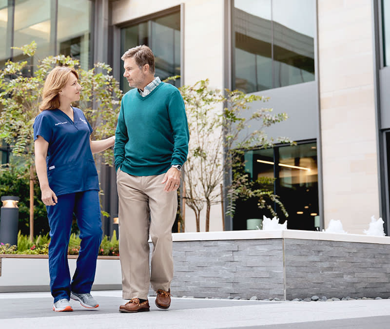 A man walks with a Baptist MD Anderson nurse, her hand touching his elbow, in the Baptist MD Anderson courtyard.