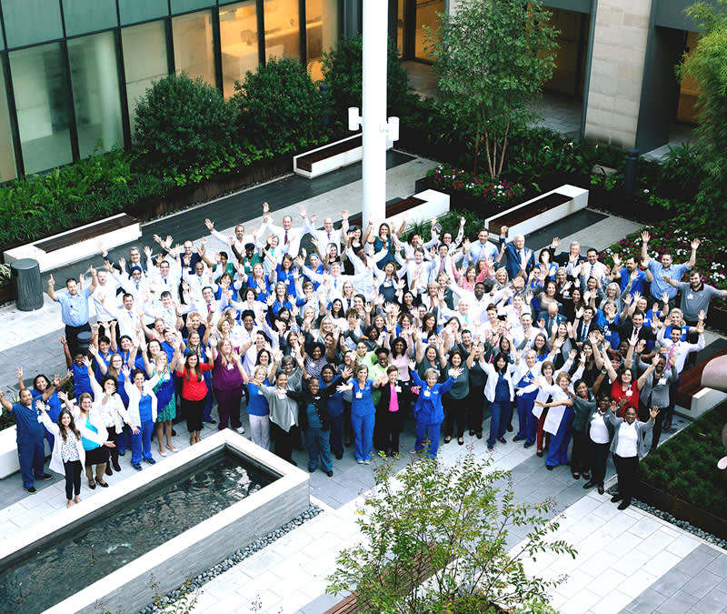 An aerial photo of a big, group of care team professionals in the Baptist MD Anderson courtyard.