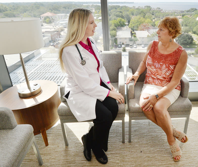 Dr. Crozier sits with a patient in front of a window, the St. John's River seem flowing in the background.