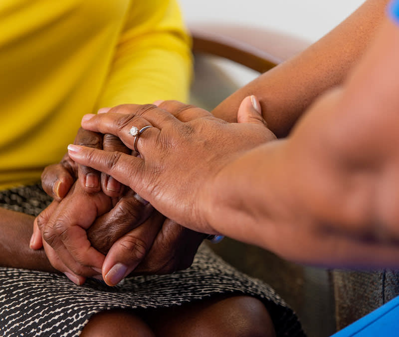 A closeup of a female nurse's hands resting on a female patient's clasped hands.