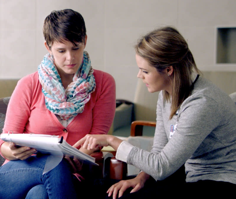 A female Baptist MDAnderson healthcare professional goes through the patient binder with a female patient.