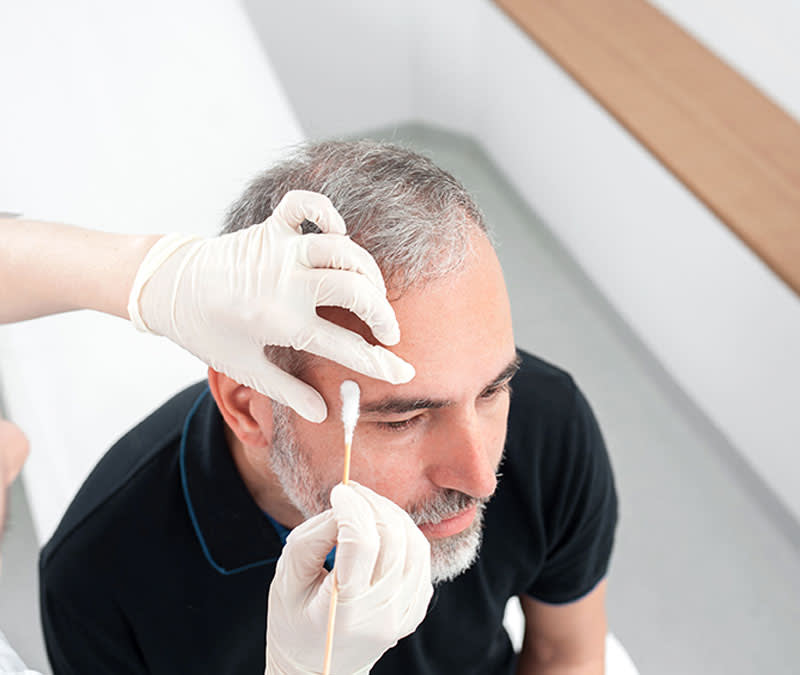 A pair of hands, wearing medical gloves, swab part of a middle-aged man's forehead.