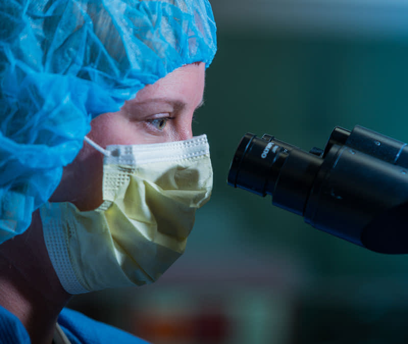 A closeup of a researcher's face, wearing mask and hair covering, looking through a microscope.