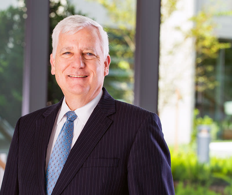 A headshot of a smiling Dr. Putnam in a suit, standing in front of the Baptist MD Anderson courtyard.