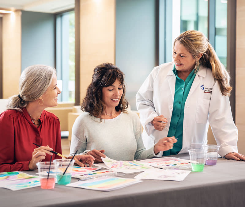 A group of patients and healthcare professional paint with watercolors.