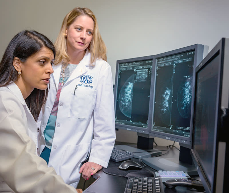 A pair of female physicians look through mammogram scans.