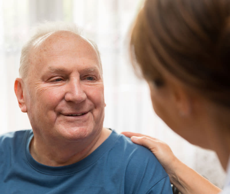 A senior man smiles at a support services professional, her hand resting gently on his shoulder.