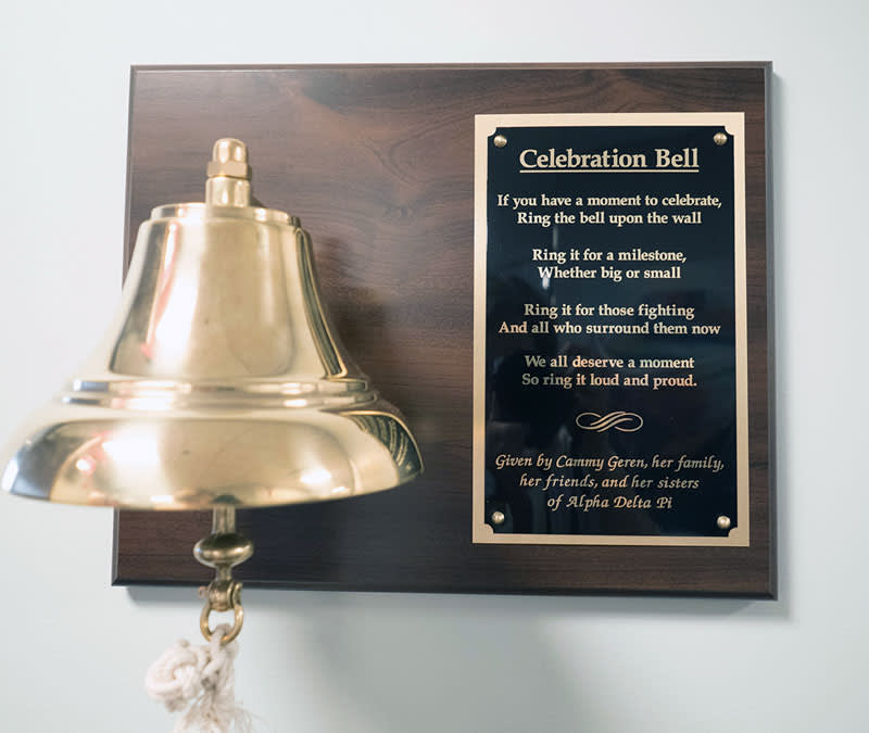 A golden bell with a plaque that says, 'Celebration Bell: If you have a moment to celebrate, ring the bell upon the wall. Ring it for a milestone, whether big or small. Ring it for those fighting, and all who surround them now. We all deserve a moment, so ring it loud and proud.'