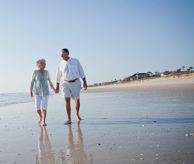 A senior couple walk along Jacksonville beach.