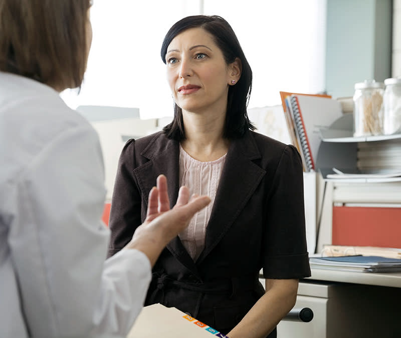 A female genetic counselor talks with a female patient.