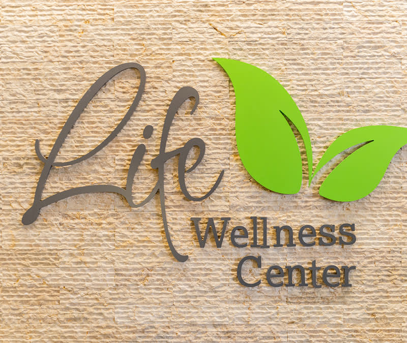 The Life Wellness Center logo affixed to a textured wall just outside the shop.