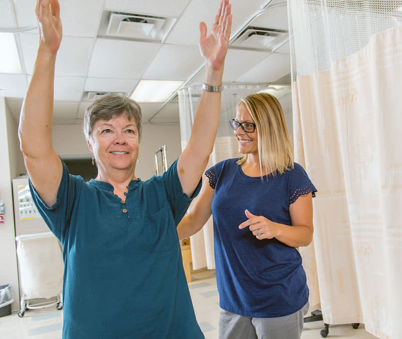 A female rehabilitation specialists works with a female patient, who stretches her arms over her head.