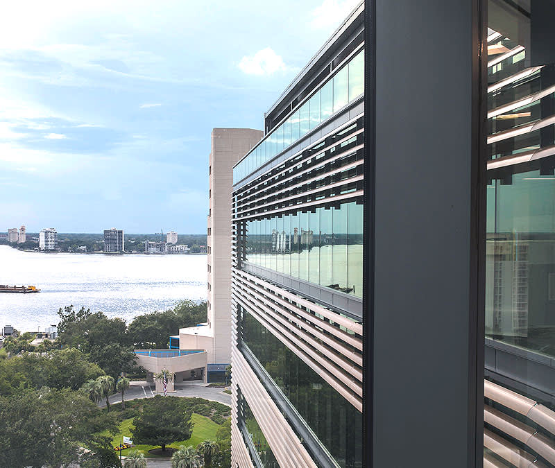 an outside shot of the Baptist MD Anderson Cancer Center, the windows reflecting the St. John's River in the background.