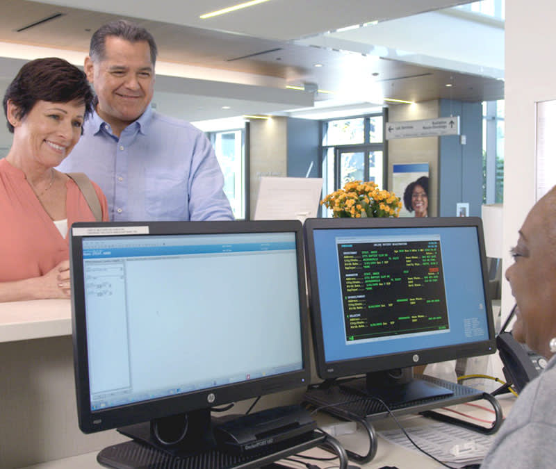 A smiling woman and her husband stand at the counter where a medical professional assists them from her desk.