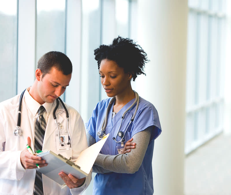 A male doctor in while coat and stethoscope looks over a file with a female nurse in scrubs.