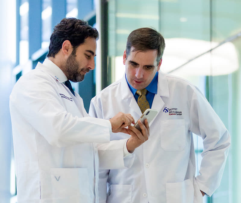 Two male physicians review information together on an iPhone.
