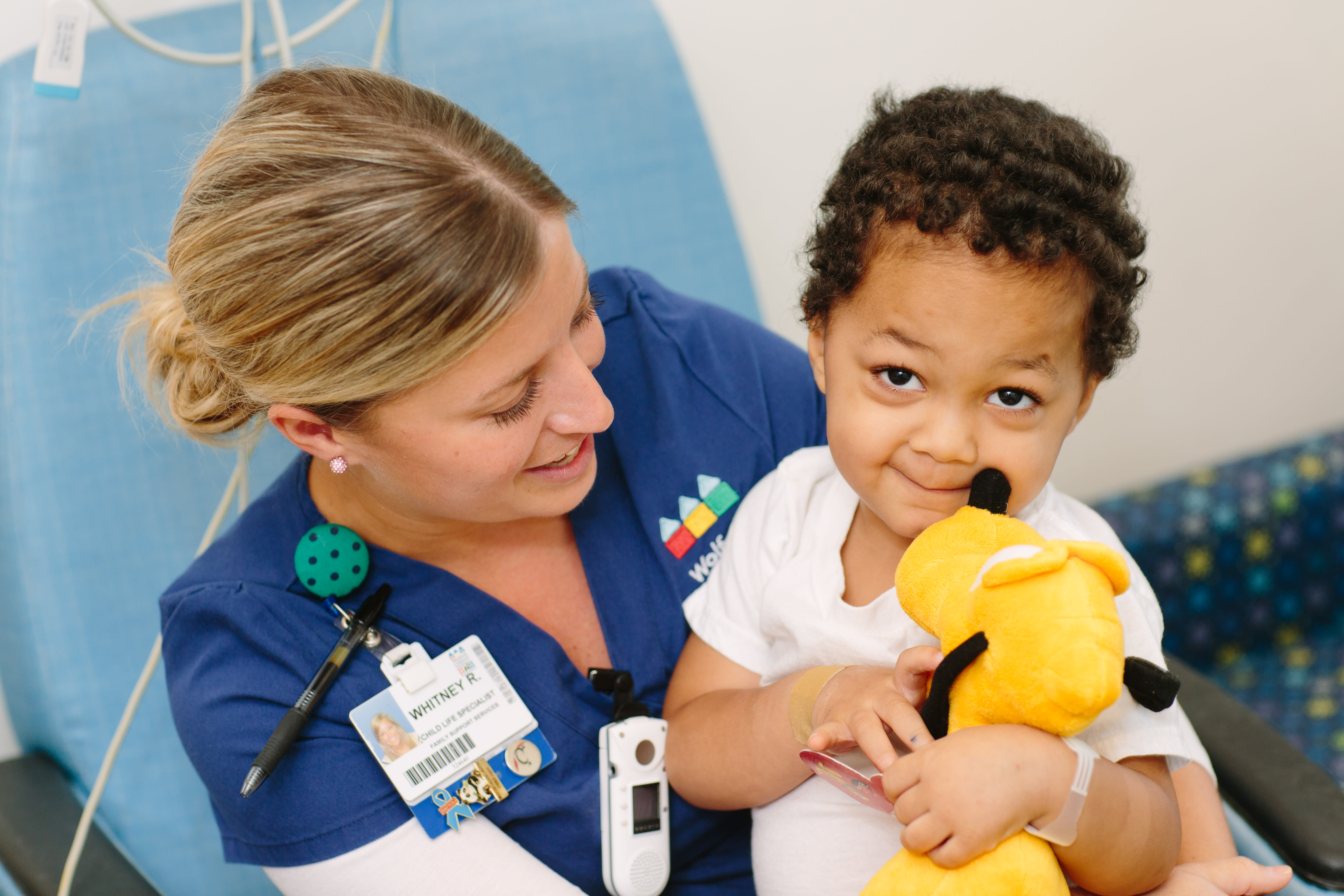 Young child with a stuffed animal being held by a nurse