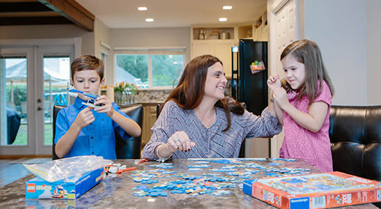 mom plays with two young children assembling a puzzle