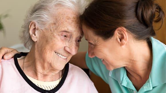 Smiling daughter hugging her elderly mom