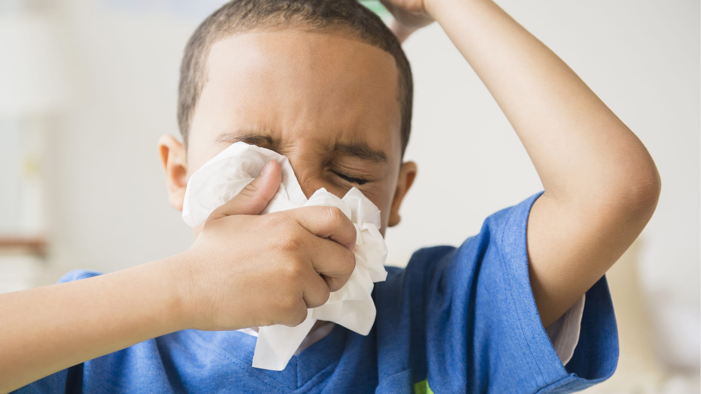 A young boy sneezes into a tissue.