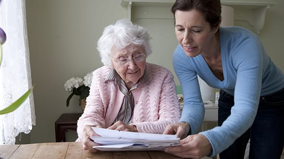 elderly woman and daughter going over paperwork