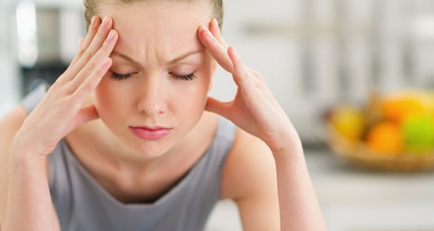 A woman clutches her head in pain