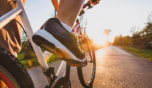 Close up shoe on bike at sunset