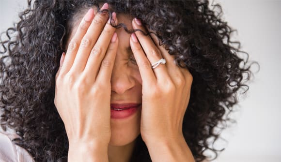 Woman holding hands over face looking embarrassed