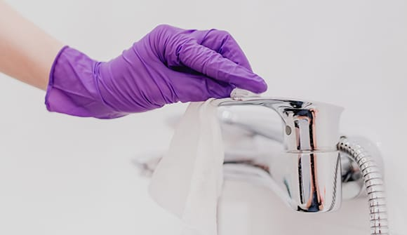 Hand in medical glove cleaning a sink