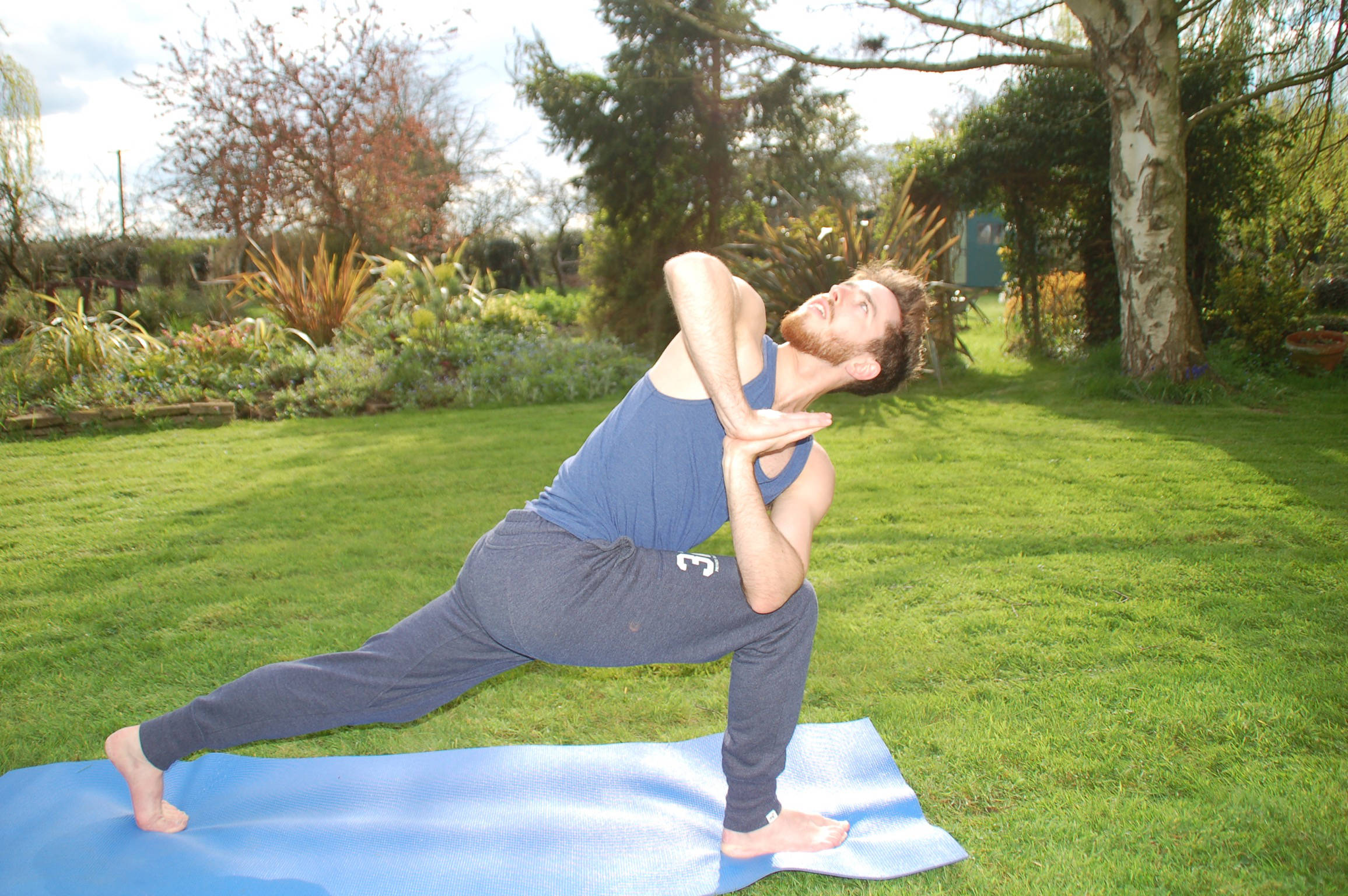 Man practicing yoga in a garden